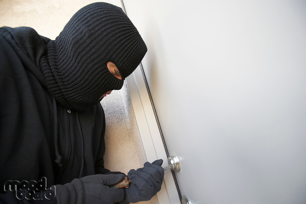 Burglar working on lock of front door