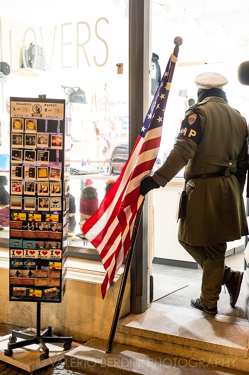 An actor embodying an american guard takes a break from posing with tourists in a souvenir shop next to checkpoint Charlie in Berlin.