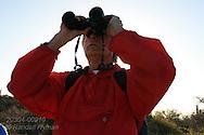 Passenger from Lindblad cruise ship birdwatches on Isla San Esteban; Sea of Cortez; Baja, Mexico.