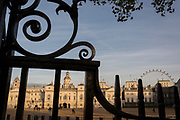Seen through iron railings is Horseguards in Westminster, on 9th November 2017, London, England. Horse Guards is a large Grade I listed historical building in the Palladian style in London between Whitehall and Horse Guards Parade. The first Horse Guards building was built on the site of the former tiltyard of Westminster Palace during 1664. It was demolished during 1749 and was replaced by the current building which was built between 1750 and 1753 by John Vardy after the death of original architect William Kent during 1748.