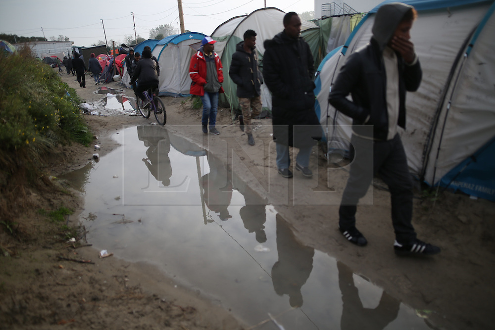 © Licensed to London News Pictures . 24/10/2016 . Calais , France . People leave the Jungle migrant camp in Calais , Northern France , on the day of a planned eviction and start of the destruction of the camp . Photo credit: Joel Goodman/LNP