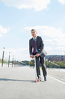 Businessman looking away while riding scooter on street