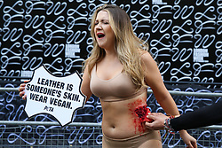 © Licensed to London News Pictures. 14/02/2020. London, UK. A half naked PETA (People for the Ethical Treatment of Animals) activist holds a sign 'Leather Is Someone's Skin. Wear Vegan' as her skin is ripped off during a protest at start of London Fashion Week against the use of animal products in the leather industry. Photo credit: Dinendra Haria/LNP