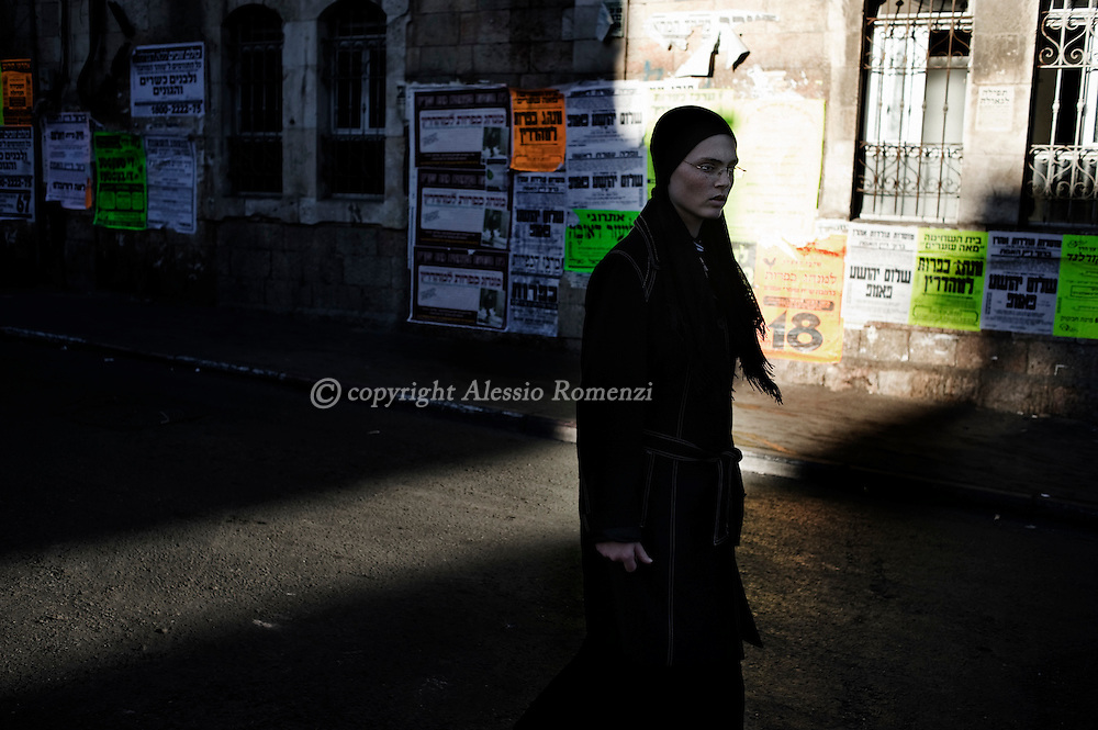 JERUSALEM : An Ultra-Orthodox Jewish girl walks during the Kaparot ceremony in Mea Shearim neighborhood of Jerusalem on October 6, 2011. The Jewish ritual is supposed to transfer the sins of the past year to the chicken, and is performed before the Day of Atonement, or Yom Kippur, the most important day in the Jewish calendar, which this year will start on sunset on October 7. ALESSIO ROMENZI