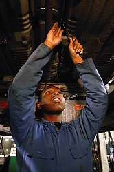 Mechanic looking at underside of a car from inspection pit,