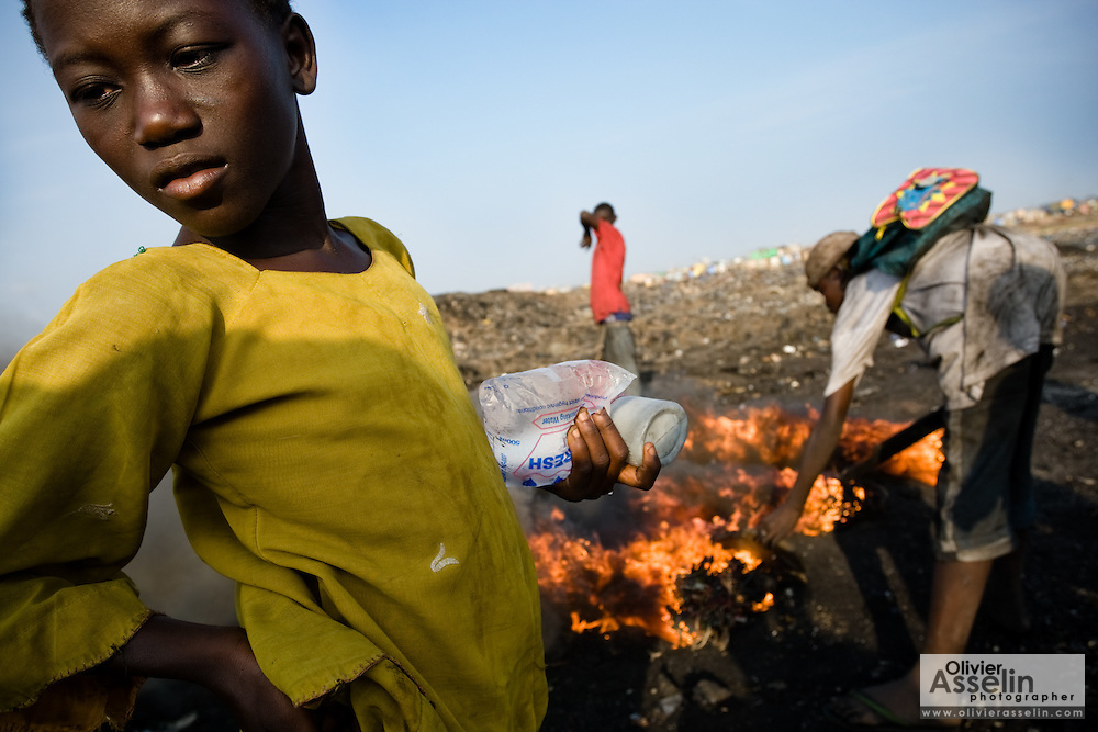 A girl who sells sachets of drinking water waits while boys burn cables from electronics to recover copper near the Agbogboloshie market in Accra, Ghana on Thursday August 21, 2008. While girls aren't directly involved in the business, they sell boys the water they use to cool off hot copper wires before handling them.