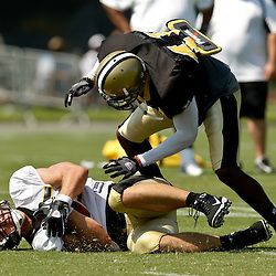July 31, 2010; Metairie, LA, USA; New Orleans Saints safety Roman Harper (41) knocks New Orleans Saints tight end David Thomas (85) to the ground following a catch during a training camp practice at the New Orleans Saints practice facility. Mandatory Credit: Derick E. Hingle