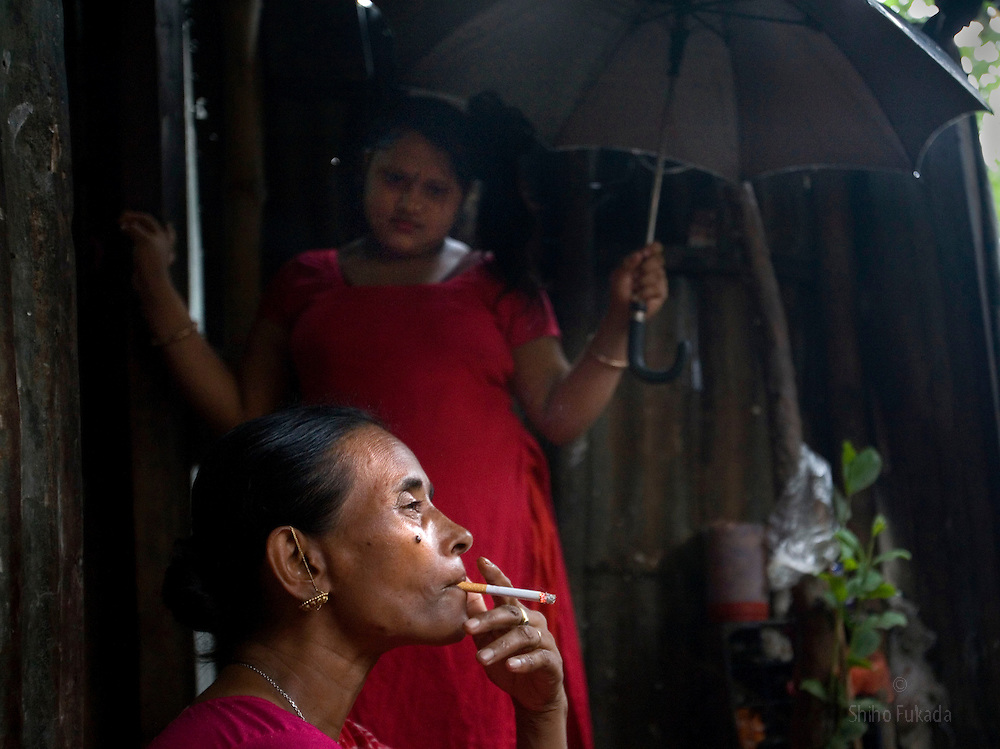 Jova, 47, foreground, smokes as her granddaughter Munnie, 15, stands by at brothel in Tangail, Bangladesh.