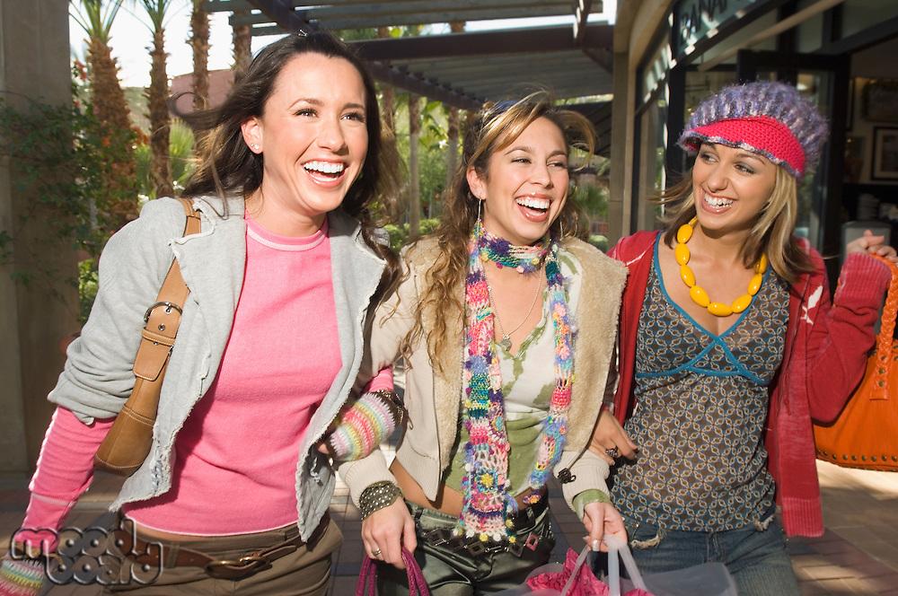 Three stylish friends walking near shopping centre
