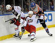 Columbus Blue Jackets' Cam Atkinson (13) falls to the ice battling for the puck with Brandon Dubinsky (17) against New York Islanders' Kevin Czuczman (24) during an NHL hockey game on Sunday, March 23, 2014, in Uniondale, N.Y. (AP Photo/Kathy Kmonicek)