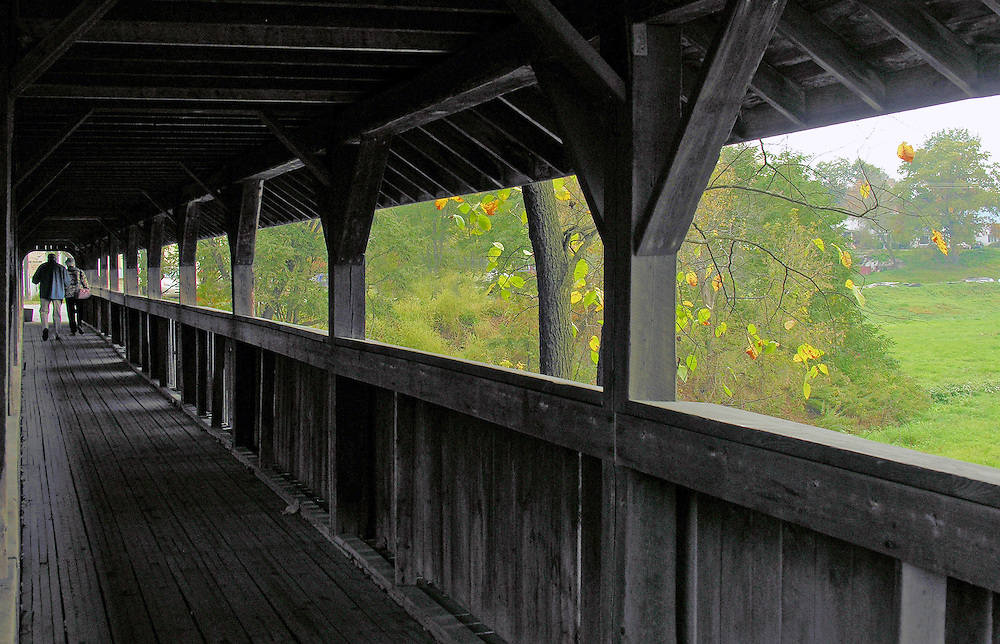 Two people walk through a covered bridge in Stowe, Vermont.