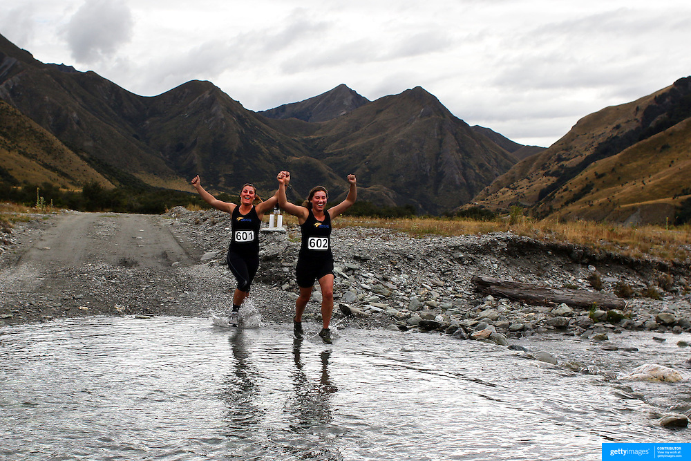 Runners Amy Tipling (left) and Grace Fleming cross Moke Creek on the Ben Lomond High Country Station during the Pure South Shotover Moonlight Mountain Marathon and trail runs. Moke Lake, Queenstown, New Zealand. 4th February 2012. Photo Tim Clayton