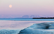 Full moon setting over Mt. Susitna and the Knik River in Southcentral Alaska. Winter. Morning.