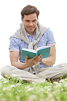 Man reading book while sitting on grass against sky