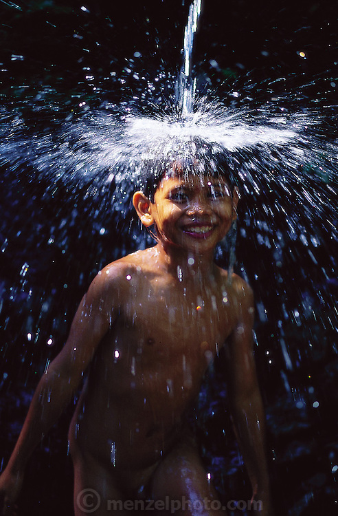 After hunting dragonflies in a rice field with a homemade bamboo whip tipped with sticky jack fruit sap, an Indonesian boy treats himself to a short swim under a waterfall, Batuan, Bali, Indonesia.(Man Eating Bugs page 61)