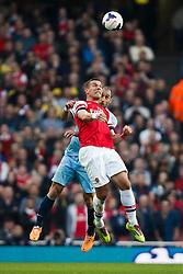 Arsenal Forward Lukas Podolski (GER) and Man City Defender Pablo Zabaleta (ARG) compete in the air - Photo mandatory by-line: Rogan Thomson/JMP - 07966 386802 - 29/03/14 - SPORT - FOOTBALL - Emirates Stadium, London - Arsenal v Manchester City - Barclays Premier League.