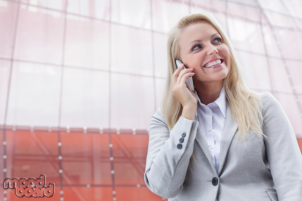 Happy young businesswoman using cell phone against office building
