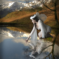 angel leaning over a blue lake