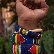 Closeup of African American woman wearing five colorful ornamental folk art beaded bracelets from Africa giving the power to the people sign.
