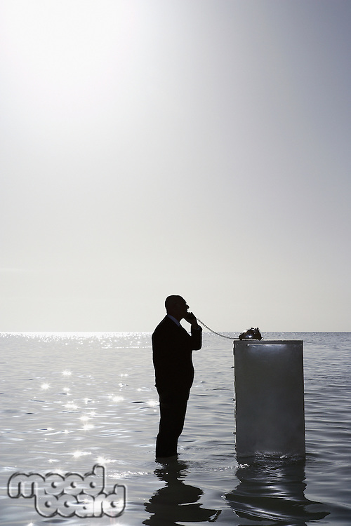 Silhouette of business man using phone on filing cabinet in sea side view elevated view