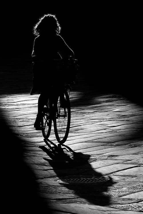 "Black and white photography of a woman on bike in Lucca Italy by Karl R Lilliendahl photographer.This photograph is available as open edition and limited edition giclee print in four sizes. Click on ""Get Print"" to see more details."