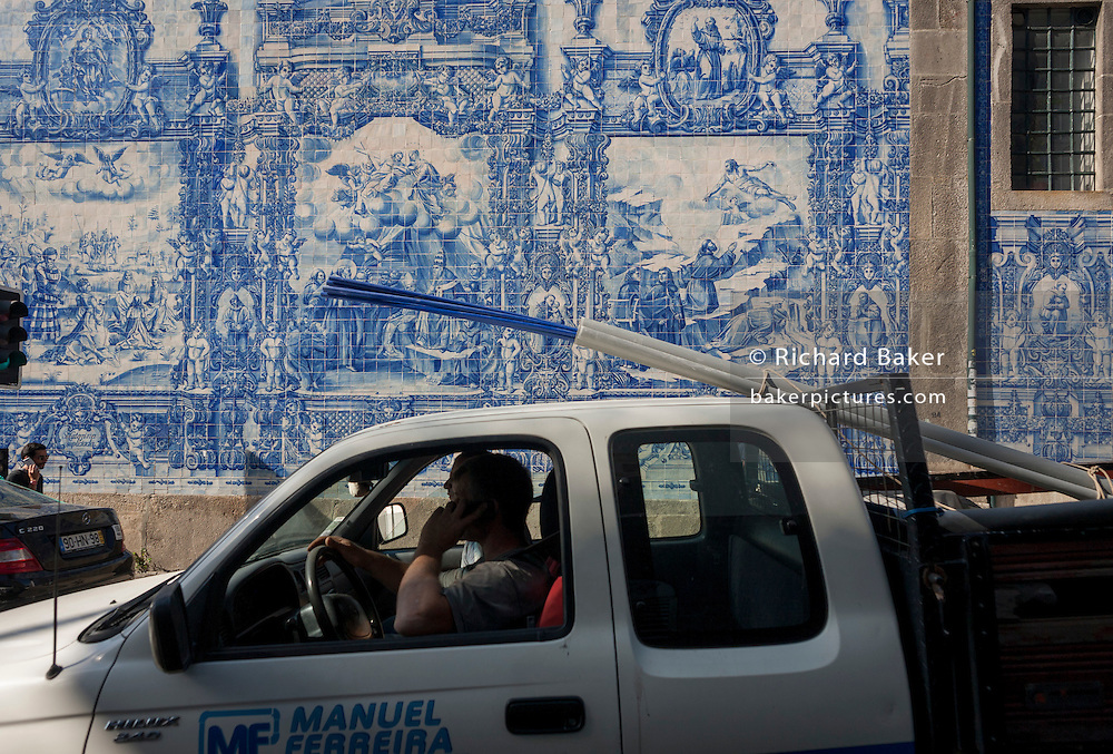 A local builder drives beneath traditional Azulejo tiles on the wall of Capela Das Almas (church), on Rua Santa Catarina Porto, Portugal. The panels depict scenes from the lives of various saints including the death of St Francis and the martyrdom of St Catherine. Eduardo Leite painted the tiles in a classic 18th-century style, though they actually date back only to the early 20th century.
