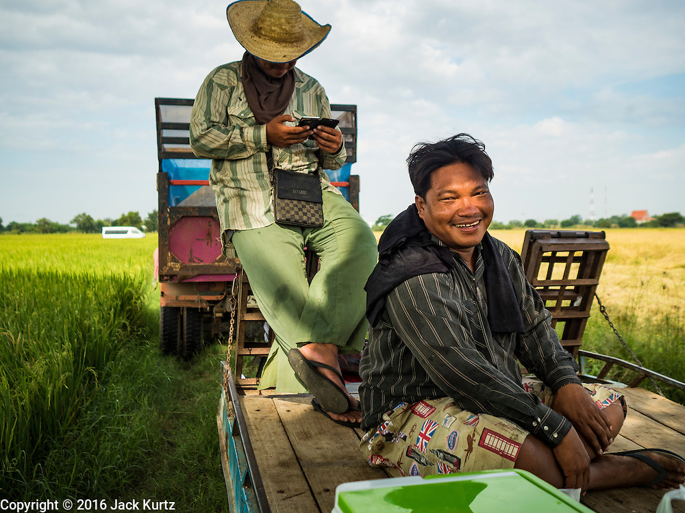 """23 NOVEMBER 2016 - AYUTTHAYA, THAILAND:   Farm workers relax during the rice harvest in Ayutthaya province, north of Bangkok. Rice prices in Thailand hit a 13-month low early this month. The low prices are hurting farmers. Rice exports account for around 10 percent of Thailand's gross domestic product, and low prices frequently lead to discontent in the rural areas of Thailand. The military government has responded by sending soldiers to rice mills, to """"encourage"""" mill owners to pay farmers higher prices. The Thai army and navy are also buying for their kitchens directly from farmers in an effort to get more money into farmers' hands.  PHOTO BY JACK KURTZ"""