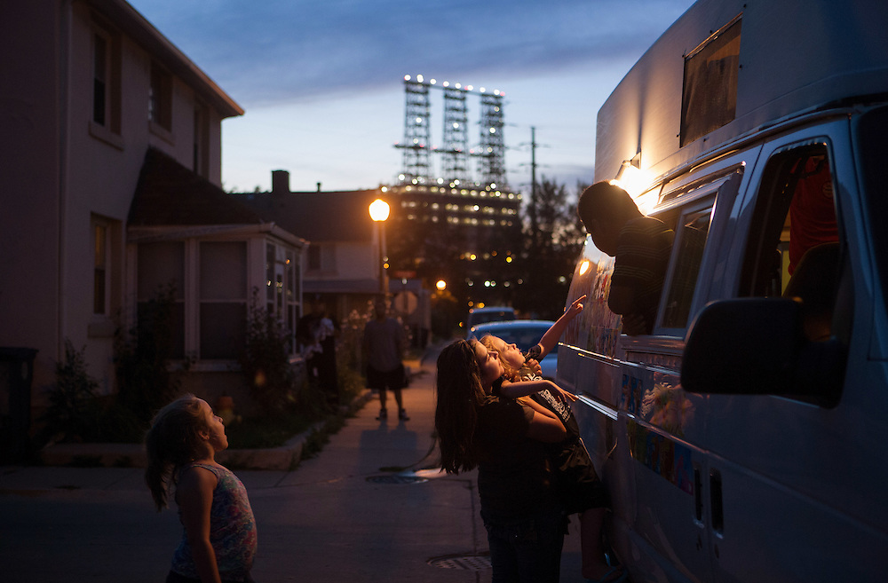 An ice cream vendor greets 11-year-old Taylor Collins with her 5-year-old sister Chloie. Their sister Gianna, 6, at left, watches. Marktown, an East Chicago neighborhood, is bordered by steel mills and a British Petroleum refinery, seen at back. <br /> <br /> <br /> --<br /> <br /> American industry disproportionately affects the health of minority and low-income communities. East Chicago, Ind. &mdash; once the country&rsquo;s &ldquo;most industrialized municipality&rdquo; &mdash; offers a view of environmental injustices emerging throughout the Rust Belt.&nbsp;<br /> <br /> Nearly 80 percent of the city&rsquo;s 11 square miles is zoned for heavy industry. Toxic levels of lead, arsenic and other pollutants contaminate water, soil and air.&nbsp;<br /> <br /> In July 2016, nearly 1,200 people in the West Calumet neighborhood learned that children had blood-lead levels six times the Center for Disease Control&rsquo;s recommendation for intervention. As mandated, residents began to move, but some remain as they struggle to find housing in the city of 29,000.&nbsp;<br /> <br /> &ldquo;We feel like we're just being thrown out,&rdquo; Nayesa Walker said. Her 3-year-old daughter&rsquo;s blood tested high for lead.&nbsp;<br /> <br /> In a letter to residents, East Chicago Mayor Anthony Copeland wrote, &ldquo;your health and safety are my first priority,&rdquo; but many say they cannot trust the government for basic services. Recently, the Environmental Protection Agency announced some of the city&rsquo;s drinking water also contains high levels of lead, prompting Indiana Gov. Eric Holcomb to declare a disaster emergency for the Superfund site just south of West Calumet.&nbsp;<br /> <br /> Two miles north, the century-old Marktown neighborhood is vanishing. British Petroleum is buying and demolishing the homes surrounding its oil refinery.&nbsp;<br /> <br /> &quot;How much money will replace 56 years' worth of memories?&quot; life-long resident Kim Rodriguez asked. &quot;I am