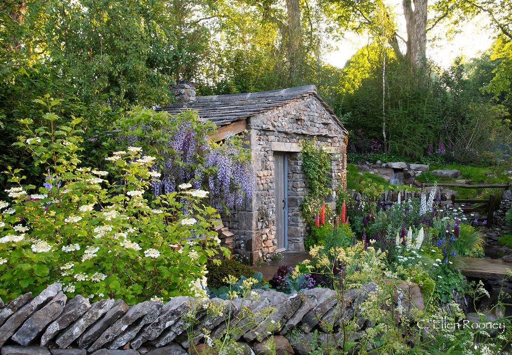 A traditional cottage style garden surrounding a stone bothy in the Welcome to Yorkshire Garden at the RHS Chelsea Flower Show 2018, London, UK