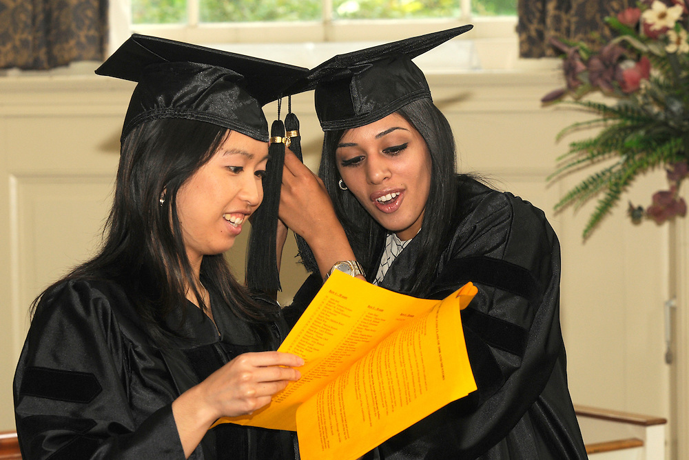 Helen Kwong, D. O., and Maryum Rafique, D. O., check out a program prior to the June 7 commencement exercises.