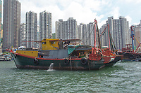 Fishing boats moored in Aberdeen fishing village with high-rise apartment blocks behind, Hong Kong, Hong Kong, August 2008   Photo: Peter Llewellyn