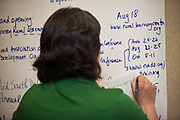 A participant writes on the note wall during the second day of the National Rural Assembly in St. Paul, MN.