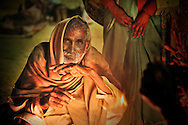 An old pilgrim after the Mauni Amavasya day, is warming near the fire.
