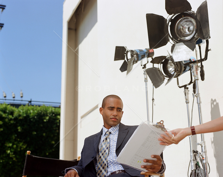 handsome actor on a Hollywood set getting a script handed to him