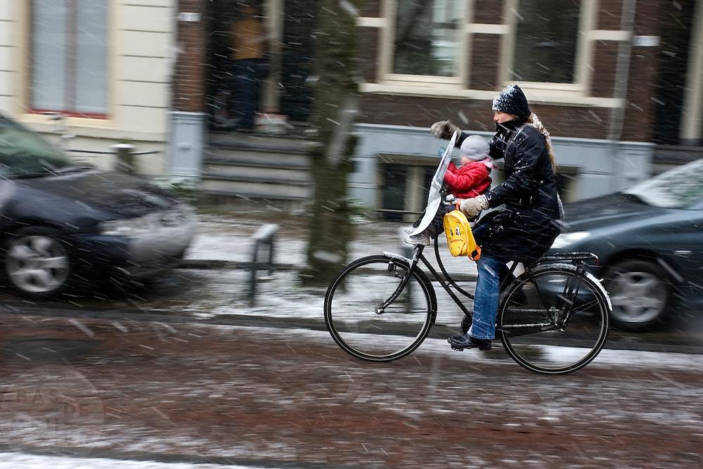 Een vrouw fietst met haar kind voorop door de sneeuw in Utrecht. Na een warme winter is het in februari eindelijk een dag winter.
