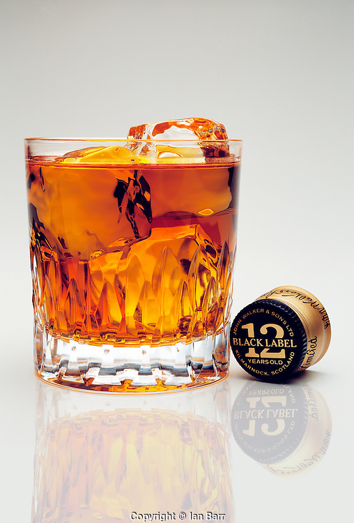 whisky glass with johnny walker black label whisky on the rocks and bottle cap.