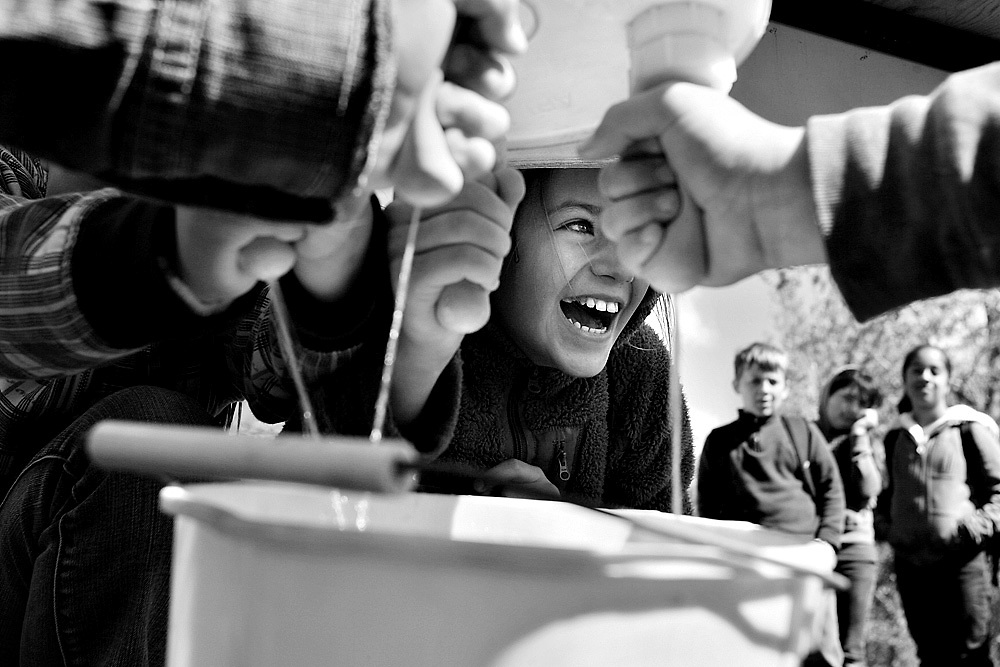 "Darya Gorbatyuk, 10, laughs as she joins her classmates from Robert Frost Elementary in Pasco in a milking competition Tuesday during the 10th annual Salmon Summit at Columbia Park in Kennewick. More than 4,000 students will participate in the two-day summit, which is co-hosted by the Benton and Franklin Conservation Districts. In addition to releasing salmon, students attended some of the 80 stations on Tuesday spanning a wide range of topics from river health to agriculture, birds of prey and Native American culture. ""Our rivers are critically important, not only for fish, but also for our way of life,"" says Rachel Little, salmon biologist and educator with the Benton Conservation District, of the summit's expanded subject matter. ""Part of why we want to diversify is to tell more sides of the story."""