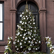 Outdoor Christmas tree with decorations in front of building.