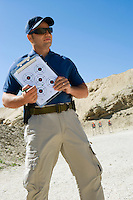 Instructor holding clipboard with target diagram at firing range