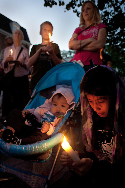 Peggy Gish ( upper left), Hyram Crawford (second from left), Rebekah Crawford (upper right), Dwiagustriani Sarasvaty (lower left) and Maharidya Neela Sarasvaty (center), participate in the candle light vigil held in in front of the Islamic Center following the interfaith march which was held to promote interfaith understanding on the anniversary of 9/11. Photo by: Ross Brinkerhoff