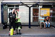 Twee goths staan bij de bushalte bij de Dom. In Utrecht komen goths uit heel Europa bij elkaar voor het jaarlijkse festival Summer Darkness. Tijdens het driedaags festijn zijn er onder andere optredens van bands, een markt en een modeshow. Het is ook een kwestie van zien en gezien worden.<br /> <br /> Two goths are waiting at the busstop nearby Summer Darkness. During the festival goths from all over Europe are coming to Utrecht to meet and enjoy music, a market, a fashion show and more.