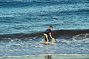 Boy playing in ocean surf with toy sailboat, Cape Cod, Massachusetts, USA