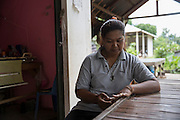 Junaporn Charoensuk, 38, sits in her small shop where she weaves cloths for extra money. On the 25th May 2016 her husband Sa-nga Hiranyabut, 40, died of Melioidosis after contracting it in his rice field. <br /> <br /> Melioidosis, though hardly heard of, is Thailand's third largest killer after AIDS and TB. Experts estimate that Melioidosis, caused by a shape-shifting bacteria that lives in water and soil, has 165,000 new cases world-wide a year and that more than half result in death. That means Melioidosis kills roughly the same number as measles or dengue across the globe. <br /> <br /> The bacteria is highly endemic in Northeast Thailand where around 2000 cases are reported per year and mostly from rice farmers who have regular contact with the soil. If not treated and the patients have other complications such a diabetes the mortality rate can be as high as 90% within 5 days.<br /> <br /> If a patient is treated, every case involves a minimum of 2 weeks in hospital followed by 20 weeks of antibiotic treatment and annual followups for the rest of their lives.<br /> <br /> Melioidosis, placed in the same microorganism grouping as anthrax by the US government, is a deadly neglected tropical disease that very few have even heard of.