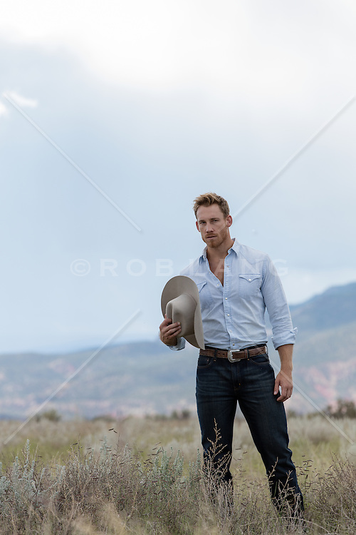 cowboy outdoors holding his hat
