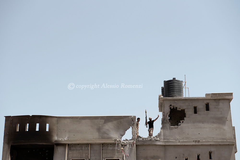 "Libya: fighters affiliated with Libya's Government of National Accord's (GNA) flashes the ""V"" of victory from a rooftop in 700 neighbourhood in Sirte. Alessio Romenzi"