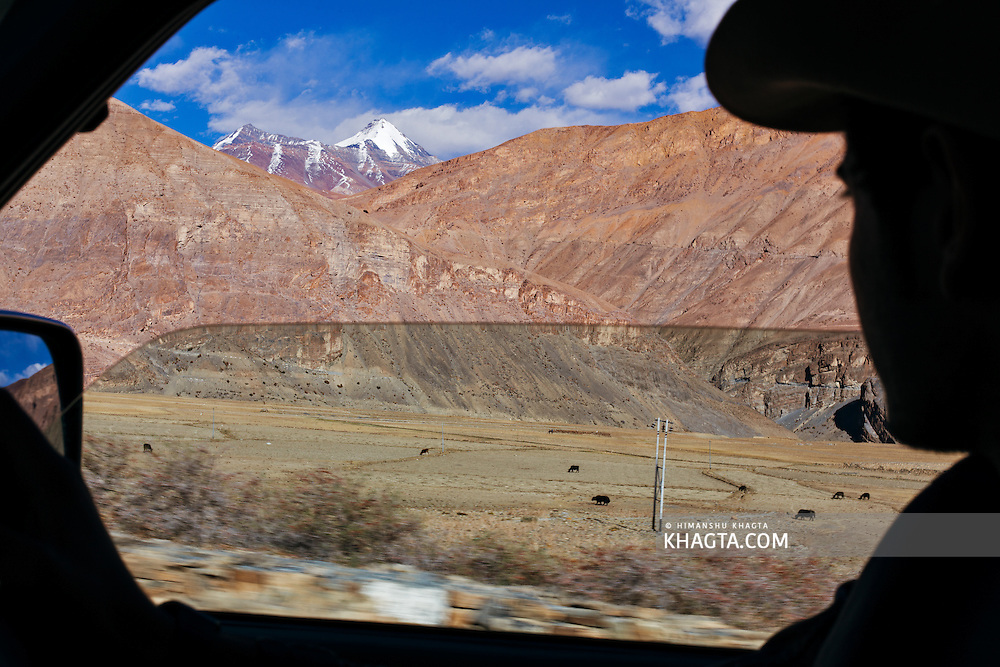 A traveler looks at Chau Chau Kang Nilda, a peak in Spiti valley from his car window