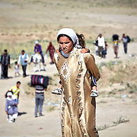 A Syrian refugee carrying a young child on her back makes her way from Syria into northern Iraq with dozens of other people at a crossing near the town of Sahela outside of Dahouk in in Iraqi Kurdistan, Wednesday, August 28, 2013. Thousands of Syrian refugees have crossed into northern Iraq in the past week.  August 2013.