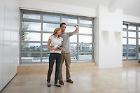 Couple photographing empty apartment