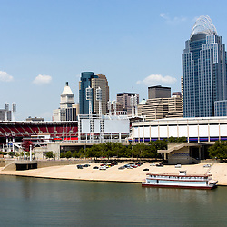 Photo of Cincinnati Ohio skyline  riverfront with a riverboat and downtown city office buildings including the Majestic Showboat, Great American Ballpark, Great American Insurance Group Tower, Omnicare building, PNC Tower building, US Bank building, US Bank Arean, and Scripps Center building. Photo was taken in July 2012.