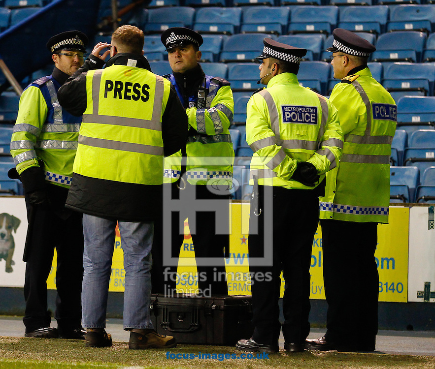 Picture by David Horn/Focus Images Ltd +44 7545 970036<br /> 03/12/2013<br /> Nottingham based photographer Dan Westwell speaks to Police Officers after being shouted at by Billy Davies , Manager of Nottingham Forest for taking photos of the bench during the Sky Bet Championship match at The Den, London.